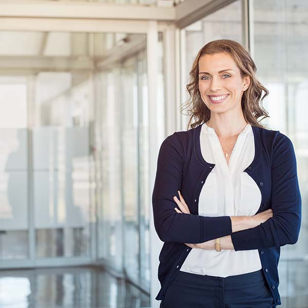 confident executive woman standing with arms crossed and smiling
