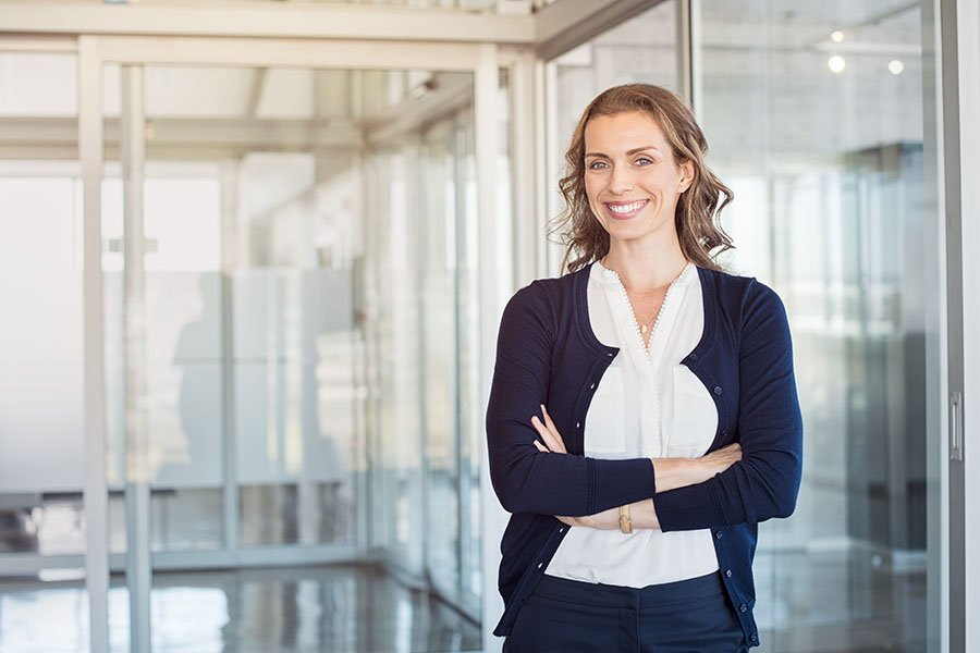 confident executive woman standing with arms crossed and smiling - for ovation coaching