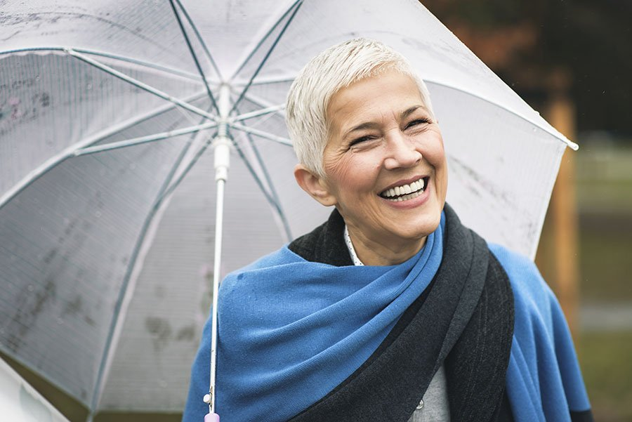 smiling senior woman with umbrella - for ovation coaching