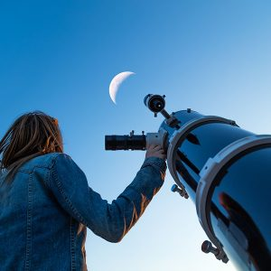 girl looking at the moon through lens
