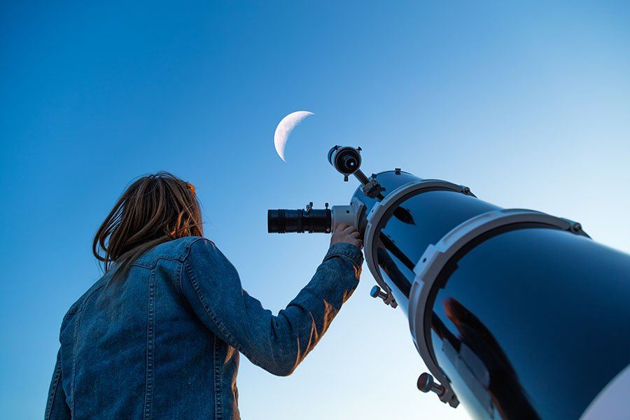 woman looking at the moon next to a telescope